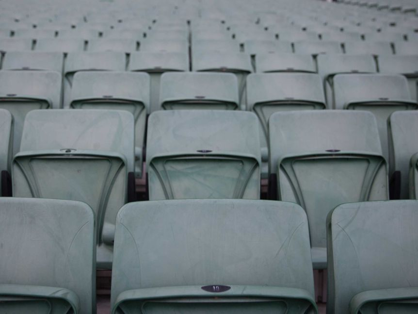 Lines of empty green seats fill the frame