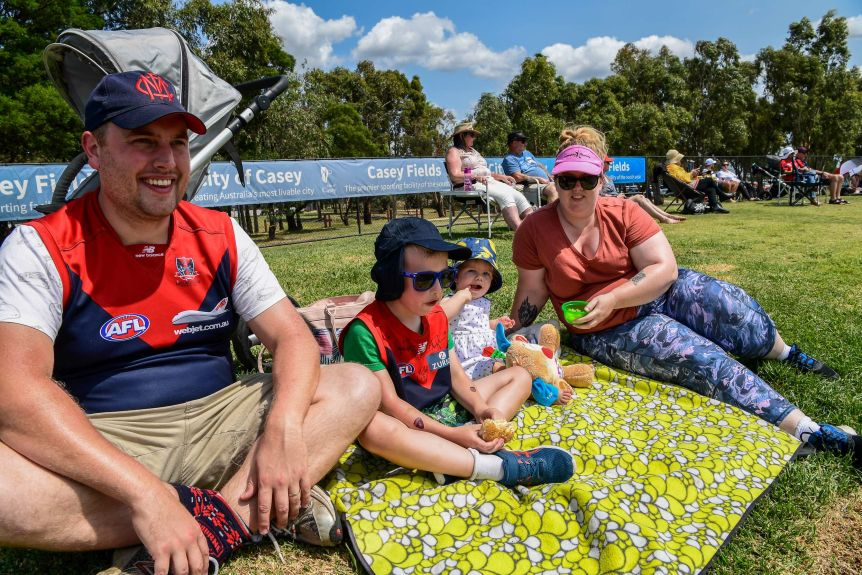 A family sits on a rug on a hill watching the AFLW.