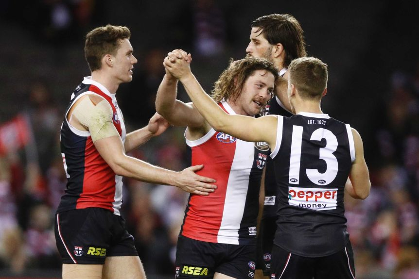 Three Saints players congratulate a smiling Jack Steven with high-fives and pats on the back.