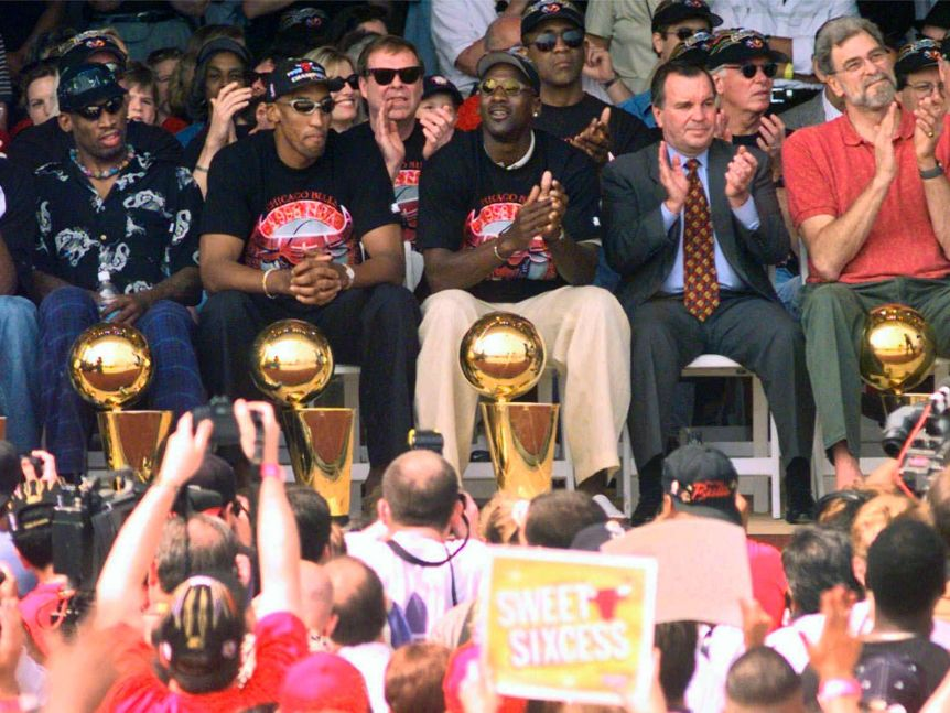 The Chicago Bulls, including Michael Jordan, sit with their NBA championship trophies at a victory parade.