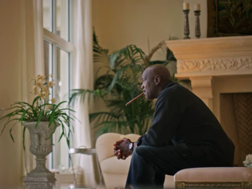 A seated Michael Jordan looks out a window while smoking a cigar during the documentary The Last Dance.