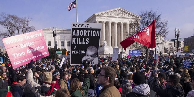 Pro-life demonstrators hold signs while marching past the U.S. Supreme Court during the 46th annual March for Life in Washington, D.C., U.S., on Jan. 18, 2019. People from around the nation gathered in Washington D.C. today for the annual rally against abortion, which included a video message from President Trump and an address by Vice President Mike Pence. Photographer: Zach Gibson/Bloomberg via Getty Images