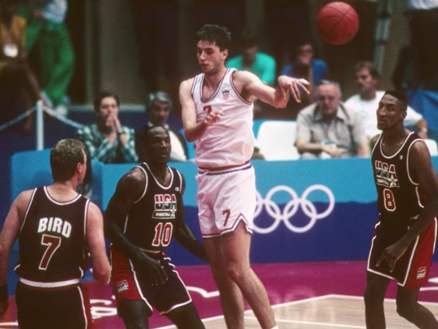 Croatia's Toni Kukoc jumps in the air to throw a pass. Larry Bird, Clyde Drexler and Scottie Pippen of Team USA surround him.