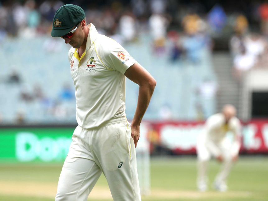 Australia fielder Pat Cummins looks down with his hands on his posterior as Nathan Lyon, blurred in the background, looks on.