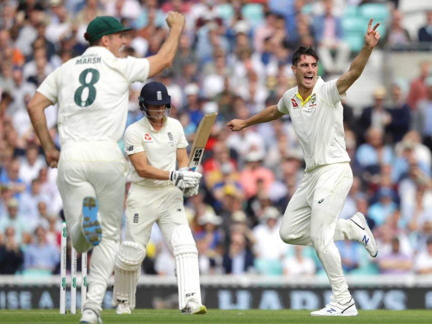 Australia bowler Pat Cummins and fielder Mitch Marsh appeal for the wicket of Joe Denly, who is between them in the frame.