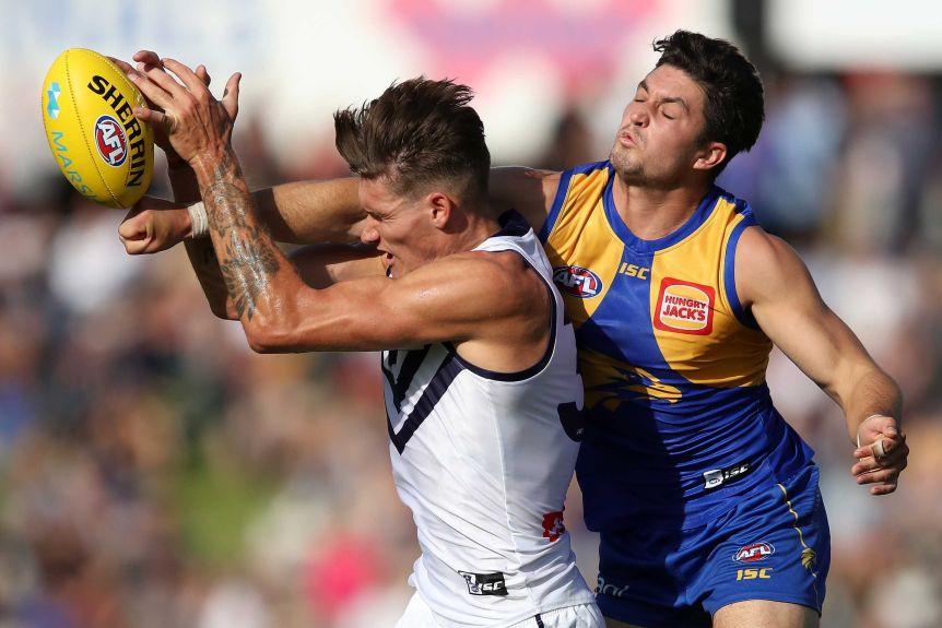 Rory Lobb comes under pressure from Tom Barrass as he tries to mark the football.