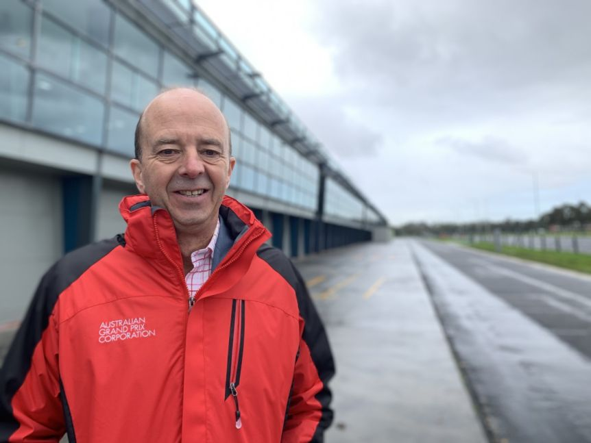 Andrew Westacott smiles, dressed in a red rain jacket out next to a motor racing track.