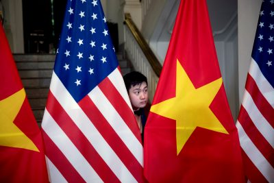 A worker helps arrange US and Vietnamese flags before US Secretary of State Mike Pompeo and Vietnamese Foreign Minister Pham Binh Minh arrive for a meeting at the Ministry of Foreign Affairs in Hanoi, Vietnam, 26 February 2019 (Photo: Reuters/Andrew Harnik).