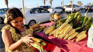 A girl carries grilled corn cobs from the stall of a pedlar on the side of a main road in Libya's capital Tripoli - 24 June 2020