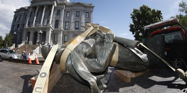 The Civil War Monument statue is strapped on the back of a flatbed tow truck after it was toppled from its pedestal in front of the State Capitol Thursday in Denver, Colorado. (AP)