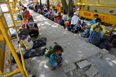 Migrant workers and their families wait to get on a bus to begin their journey home amid an extended lockdown to slow the spread of COVID-19 in New Delhi, India, 26 May 2020 (Photo: Reuters/Adnan Abidi).