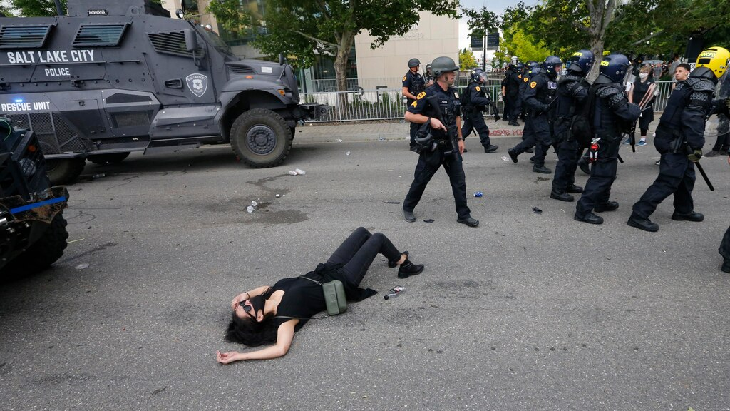 An injured protester lays on the ground as police push forward during a protest in Salt Lake City.