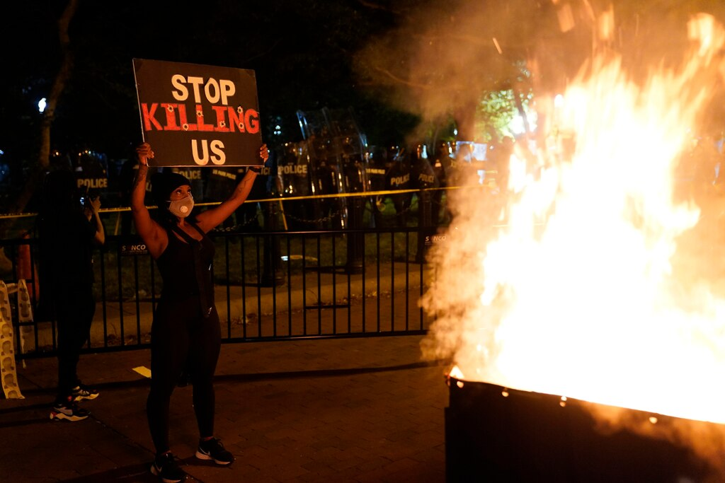 A fire burns in a dumpster as demonstrators protest the death of George Floyd near the White House in Washington.