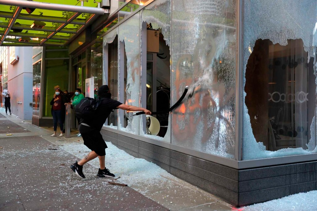 A protester breaks a window in downtown Chicago during violent protests.