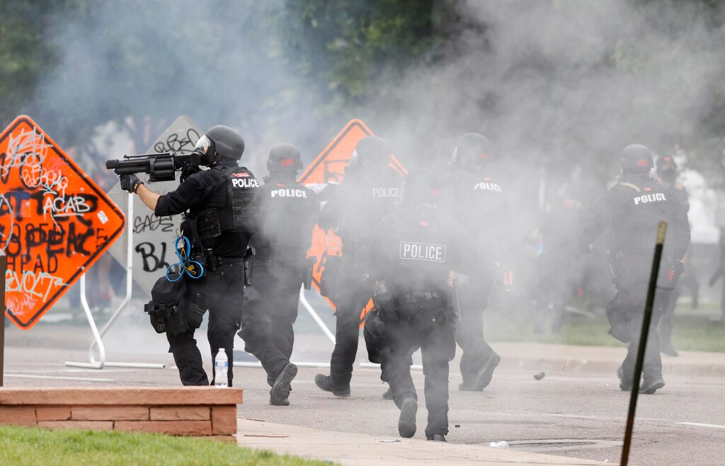 Denver Police fire tear gas canisters during a protest outside the State Capitol.