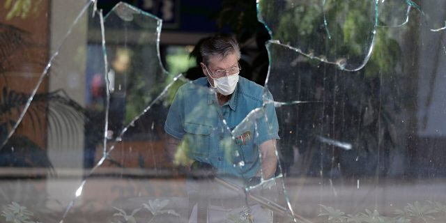 A worker vacuums broken glass from storefront in downtown Louisville, Ky. , Saturday, May 30, 2020. The store was damaged Friday evening during a protest over the deaths of George Floyd and Breonna Taylor. (AP Photo/Darron Cummings)