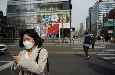 A woman wearing a mask to prevent the coronavirus uses her mobile phone at a shopping district in Seoul, South Korea, 24 February, 2020 (Photo: Reuters/Kim).