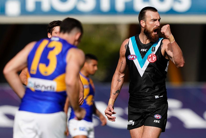 A Port Adelaide AFL player pumps his left fist as he celebrates kicking a goal against West Coast.