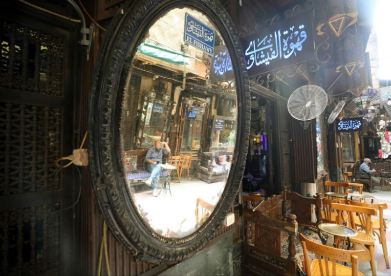 """Al-Fishawy cafe in Cairo, Egypt, 27 June 2020. Egyptian authorities decided to ease coronavirus restrictions gradually. Cafes and restaurants are back to business starting from 27 June 2020, but they must operate at 25% of their capacity and observe social distancing among other safety measures, and any violations will result in the suspension of the facility""""s activities."""