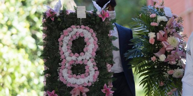 A man carries flowers into a viewing for 8-year-old Secoriea Turner, who was fatally shot in Atlanta on July 4th near the Wendy's site where Rayshard Brooks was killed the previous month. (AP Photo/John Bazemore)