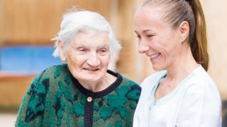 An elderly lady with a helper
