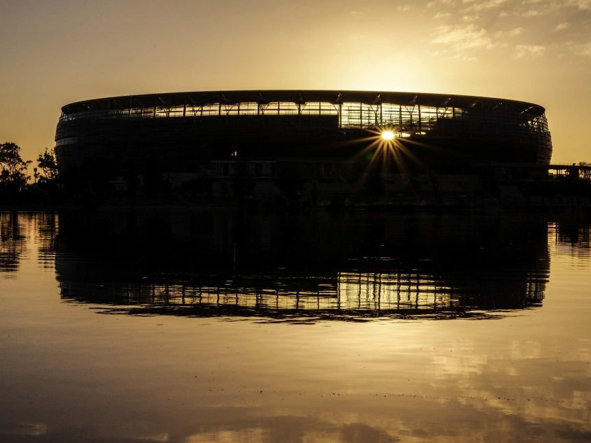 Perth Stadium in silhouette at sunrise.