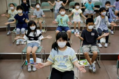 Students wearing protective face masks amid the coronavirus disease (COVID-19) outbreak, clap along instead of singing a song during a music class at Takanedai Daisan elementary school, which practices various methods of social distancing in order to prevent the infection, in Funabashi, east of Tokyo, Japan 16 July, 2020 (Photo: Reuters/Kim).