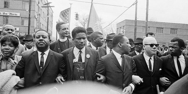 In this March 17, 1965, file photo, Dr. Martin Luther King Jr., fourth from left, foreground, locks arms with his aides as he leads a march of several thousands to the courthouse in Montgomery, Ala. From left are: an unidentified woman, Rev. Ralph Abernathy, James Foreman, King, Jesse Douglas Sr., and John Lewis. Lewis, who carried the struggle against racial discrimination from Southern battlegrounds of the 1960s to the halls of Congress, died Friday, July 17, 2020.