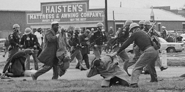 In this March 7, 1965, file photo, a state trooper swings a billy club at John Lewis, right foreground, chairman of the Student Nonviolent Coordinating Committee, to break up a civil rights voting march in Selma, Ala. Lewis sustained a fractured skull. Lewis, who carried the struggle against racial discrimination from Southern battlegrounds of the 1960s to the halls of Congress, died Friday, July 17, 2020.