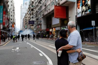 A couple hugs each other as police fire tear gas into the crowds to disperse anti-national security law protesters during a march on the anniversary of Hong Kong's handover from Britain to China, Hong Kong, 1 July 2020 (Photo: Reuters/Tyrone Siu).