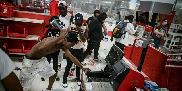 In this Wednesday, May 27, 2020 photo, a looter uses a claw hammer as he tries to break in to a cash register at a Target store in Minneapolis. Rioters ignited fires and looted stores all over the city, as peaceful protests turned increasingly violent in the aftermath of the death of George Floyd. (Richard Tsong-Taatarii/Star Tribune via AP)