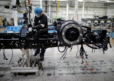 An employee wearing a protective face mask and face guard works on the automobile assembly line as the maker ramps up car production with new security and health measures as a step to resume full operations, during the outbreak of COVID-19 at Kawasaki factory of Mitsubishi Fuso Truck and Bus Corp, in Kawasaki, south of Tokyo, Japan, 18 May 2020 (Photo: Reuters/Issei Kato).