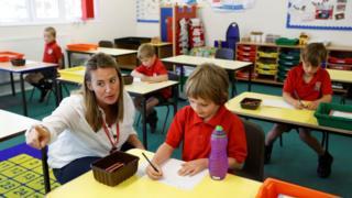 A teacher talks to a child at Watlington Primary School as some schools re-open, following the outbreak of the coronavirus disease (COVID-19), Watlington