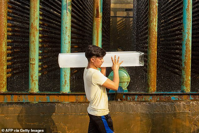 A labourer carries a block of ice at a factory in the southern Iraqi port city of Basra amid sweltering temperatures