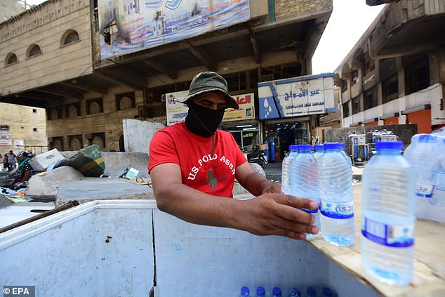 An Iraqi street vendor sells cold water bottles during a sweltering hot day at the Al-Khilani square in central Baghdad earlier this week