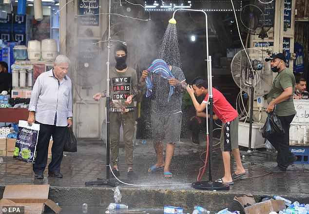 BAGHDAD, IRAQ: Men cool off under outdoor showers as temperatures rise to almost 125F (52C) earlier this week
