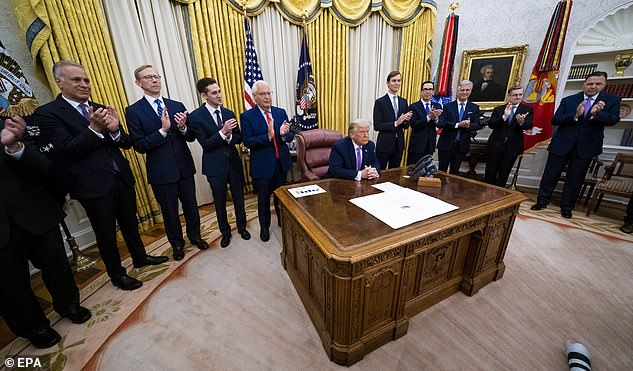 Officials applaud after President Trump announced the deal