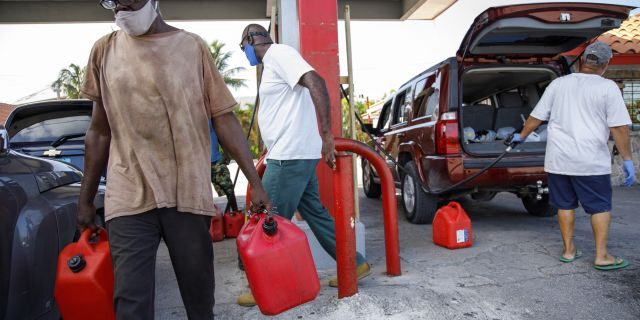 A resident walks with containers filled with gasoline at Cooper's gas station before the arrival of Hurricane Isaias in Freeport, Grand Bahama, Bahamas, Friday, July 31, 2020. (AP Photo/Tim Aylen)