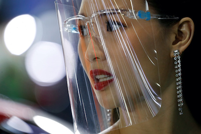 A promoter wears a face shield during the 41st Bangkok International Motor Show, after the Thai government eased measures to prevent the spread of the coronavirus disease (COVID-19), in Bangkok, Thailand, 15 July, 2020 (Photo: Reuters/Silva).