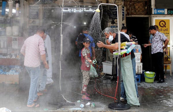 Cooling off under an outdoor shower in Baghdad.