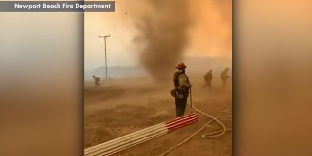A smoke dust devil rages as firefighters battle the El Dorado wildfire in California.