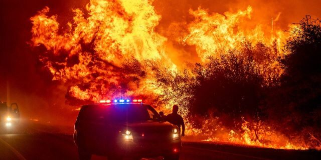Flames lick above vehicles on Highway 162 as the Bear Fire burns in Oroville, Calif., on Wednesday, Sept. 9, 2020.