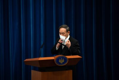 Yoshihide Suga removes his face mask as he arrives to attend a press conference following his confirmation as Prime Minister of Japan, in Tokyo, Japan, 16 September, 2020 (Carl Court/Pool via Reuters).