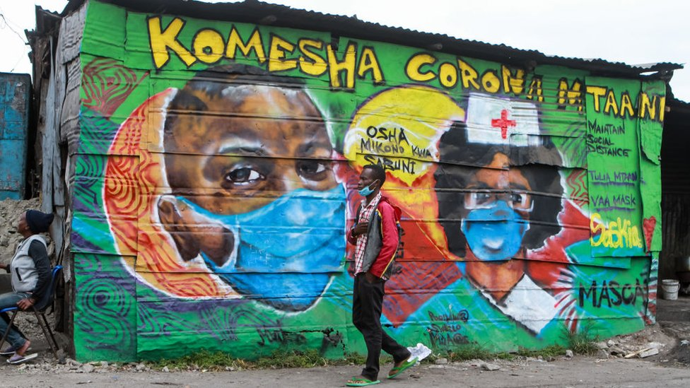A man wearing a face mask walks past a mural depicting health workers by the Mathare Roots Society initiative group that uses the graffiti form of creative art to inform and sensitise the residents of Mathare slums.