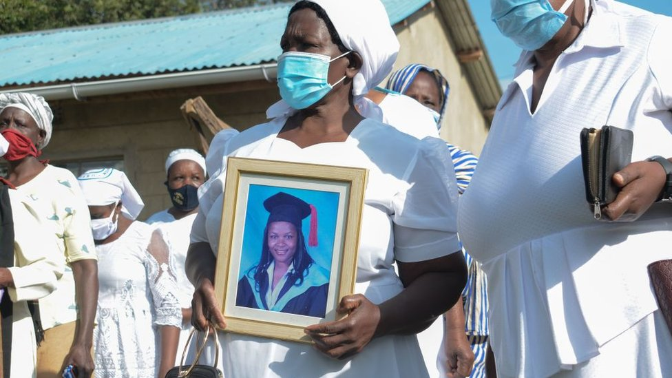 Grace Lugaliki (2nd R) holds a portrait of her daughter Dr. Doreen Lugaliki, 39, the first Kenyan doctor who died of the COVID-19 coronavirus in Nairobi, during her daughter's funeral in Ndalu, western Kenya, on July 13, 2020