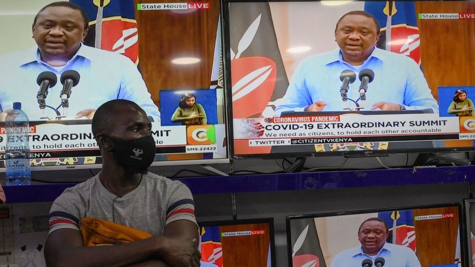 A man wearing a face mask stands inside an electronics shop as Kenya's President Uhuru Kenyatta is seen on television screens while giving an address to the nation on the COVID-19 (novel coronavirus) pandemic, and measures that the government maintain and enforce to curb the disease's spread, on July 27, 2020, in Nairobi