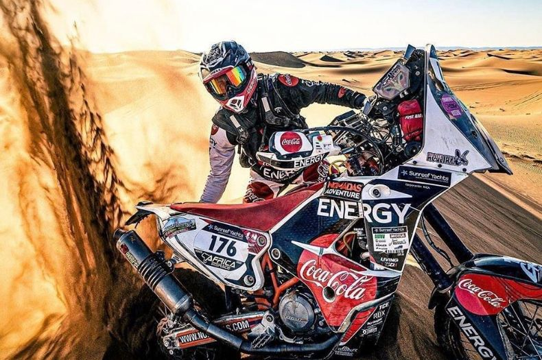 Rider Andrew Houlihan riding through sand dunes in an African dessert