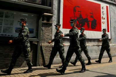 Chinese servicemen walk past portraits of German philosophers Karl Marx and Friedrich Engels and patrol a street near the Great Hall of the People on the opening day of the National People's Congress (NPC) following the outbreak of the coronavirus disease (COVID-19), in Beijing, China 22 May, 2020 (Photo:Reuters/Thomas Peter).