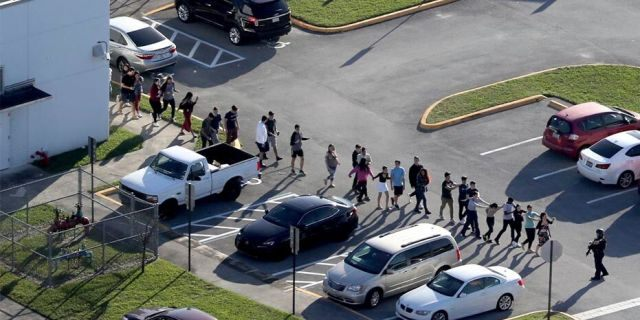 Students are evacuated by police from Marjory Stoneman Douglas High School in Parkland, Fla., during a February 2018 mass shooting that killed 17 students and staff. On Thursday, the state Supreme Court capped compensation at $300,000 for families and victims who filedlawsuits against the Broward County School Board over the incident.