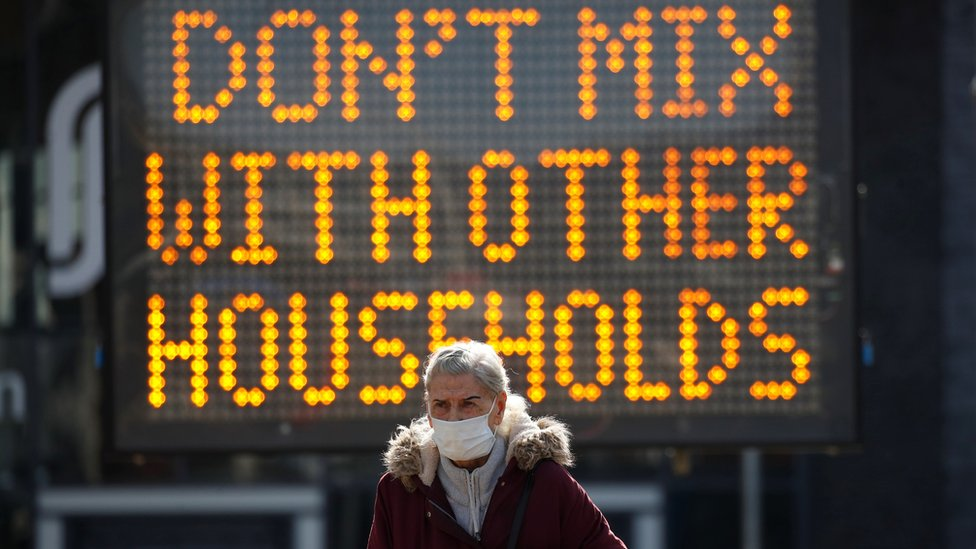 """Woman in front of sign, which reads """"Don't mix with other households"""""""